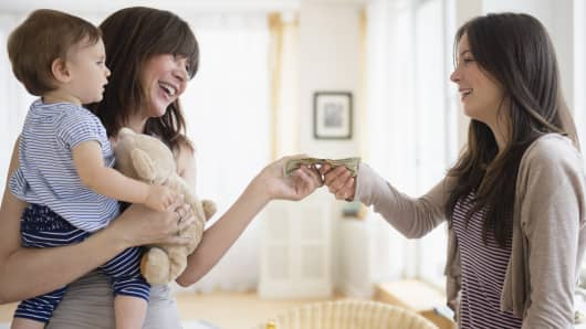 Premium: mother paying babysitter
