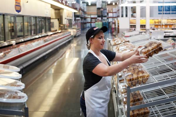 A bakery employee distributes baked goods onto a display rack inside a Costco Wholesale store in Nashville, Tennessee.