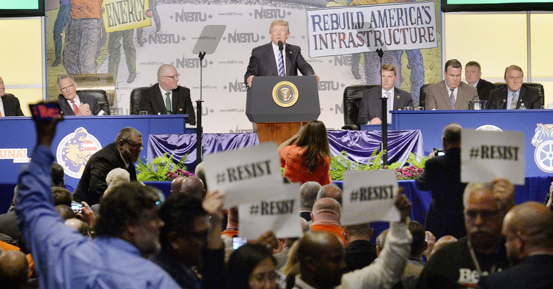 US President Donald Trump makes remarks as protester hold signs at the 2017 North America's Building Trades Unions National Legislative Conference at the Washington Hilton on April 4, 2017