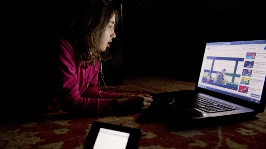 A girl stares at her computer screen