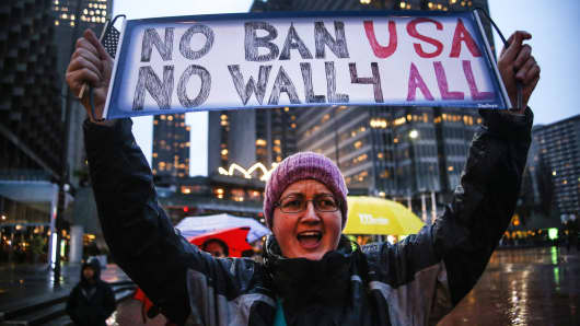 A woman shouts slogans and holds a placard during a rally in downtown against President Donald Trump's ICE and deportation programs in San Francisco, on February 17, 2017.