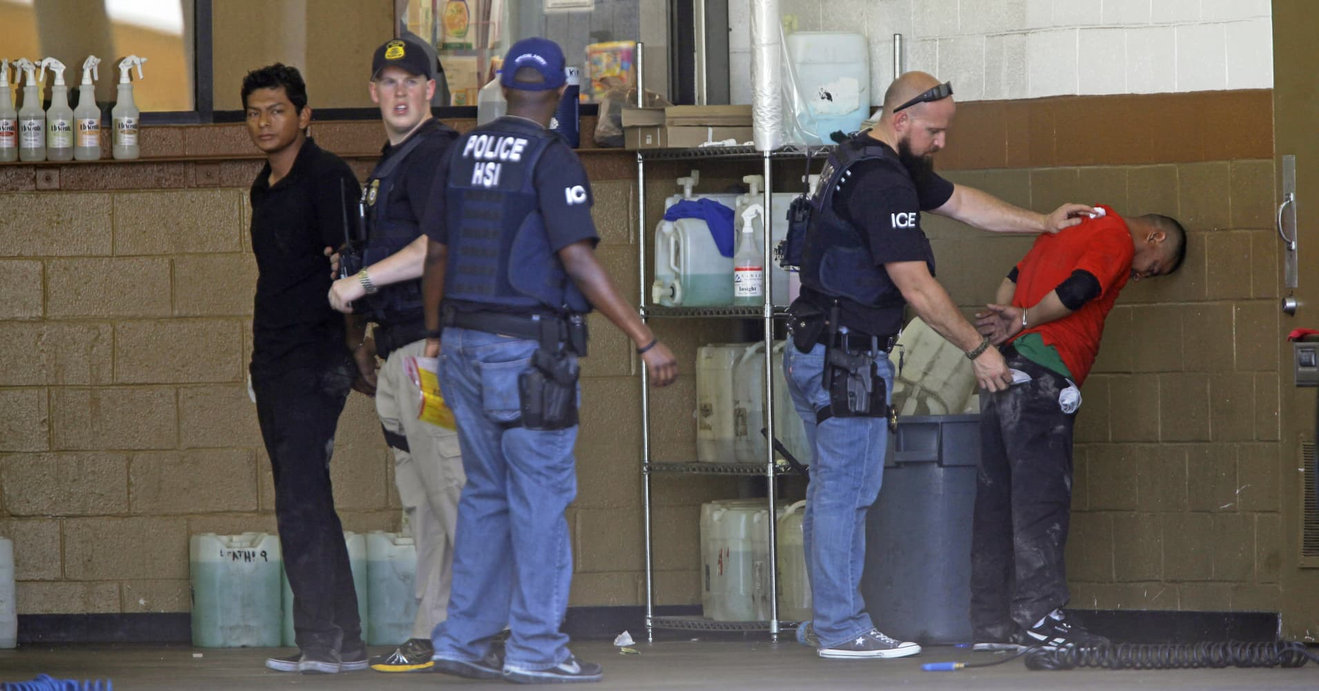 ICE agents detain workers outside a business.