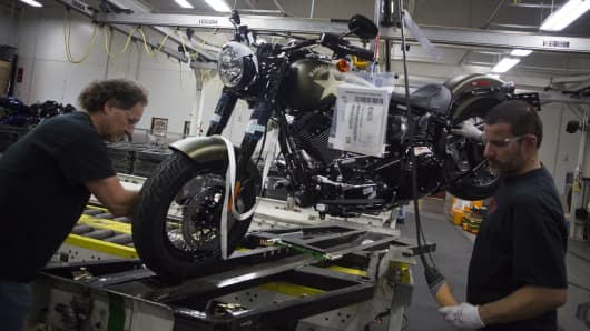 Employees lift a motorcycle up to the shipping area on the assembly line at the Harley-Davidson Inc. manufacturing facility in York, Pennsylvania, U.S., on Tuesday, Nov. 3, 2015.