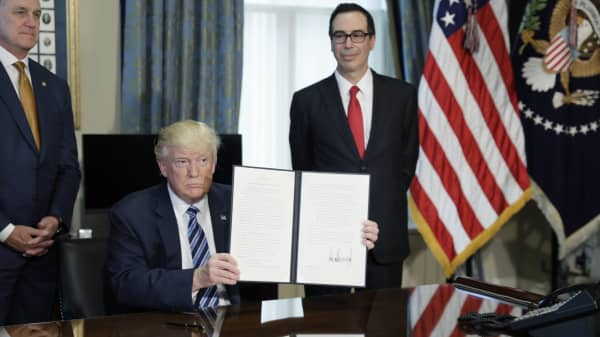 President Donald Trump (C) displays a financial services executive order as Treasury Secretary Steven Mnuchin (R) looks on during a signing ceremony at the Treasury Department in Washington, U.S., April 21, 2017.