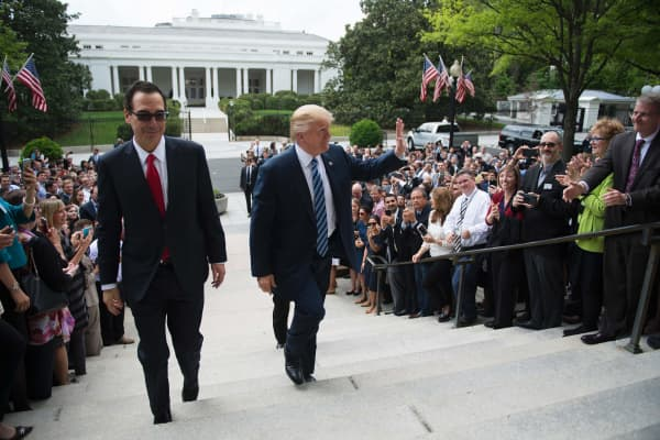 President Donald Trump (C) waves with Treasury Secretary Steven Mnuchin (L) as they walk from the White House to the US Treasury Department in Washington, DC, April 21, 2017.