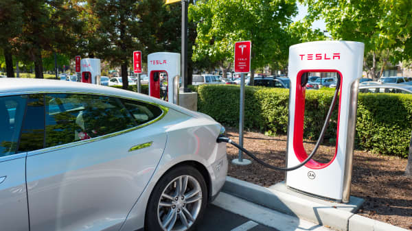 Tesla automobile plugged in and charging a Supercharger rapid battery charging station for the electric vehicle company Tesla Motors, in the Silicon Valley town of Mountain View, California.