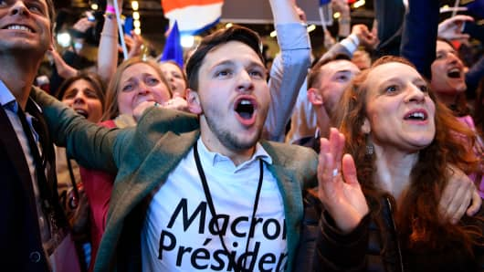 Supporters of French presidential election candidate Emmanuel Macron celebrate after the results of the first round of the presidential election, on April 23, 2017 at the Parc des Expositions in Paris.