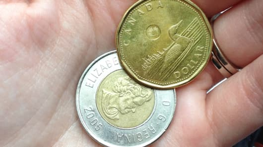 A man holds Canadian Loonie and Toonie coins.
