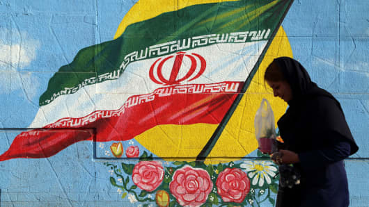 A Iranian woman walks past a wall painting in the shape of Iranian flag in Tehran Iran on the first anniversary of nuclear deal between Iran and world powers