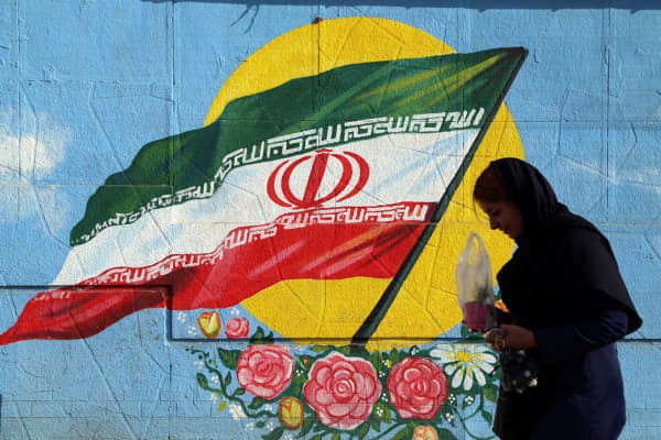 A Iranian woman walks past a wall painting in the shape of Iranian flag in Tehran, Iran on the first anniversary of nuclear deal between Iran and world powers on January 16, 2017.