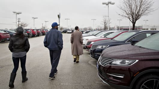 A couple walks with a salesman, right, while shopping for a new vehicle at the Sutton Ford Lincoln car dealership in Matteson, Illinois.