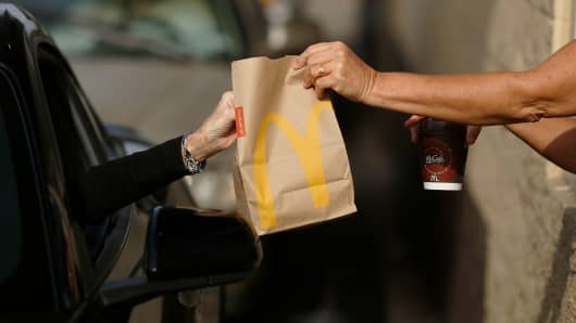 A worker passes a bag of food to a customer at the drive-thru window at a McDonald's fast food restaurant in White House, Tennessee.