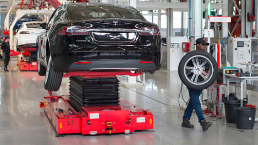 An employee removes a wheel from a Tesla Model S automobile during driving unit fitting on the final assembly line at the Tesla Motors Inc. factory in Tilburg, Netherlands.