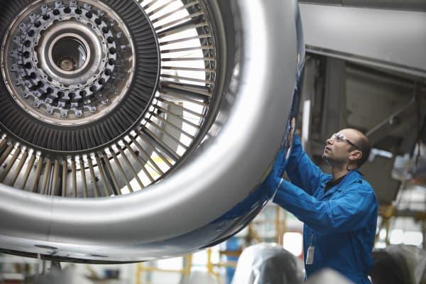 An aerospace engineer works on a plane.