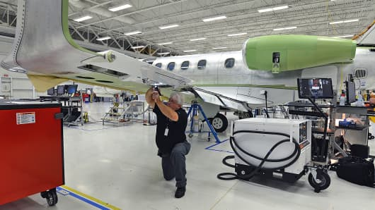 Quality assurance inspector Mike Pettis inspects a flap assembly on an Embraer SA Phenom 300 Light business jet in Melbourne, Florida.