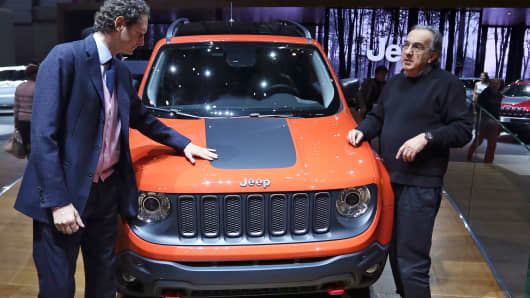 John Elkann, chairman of Fiat SpA, center left, and Sergio Marchionne, chief executive officer of Fiat SpA and Chrysler Group LLC, center right, look at the new Jeep Renegade SUV automobile, produced by Chrysler Group LLC, as it stands on display at the company's stand on the opening day of the 84th Geneva International Motor Show in Geneva, Switzerland.