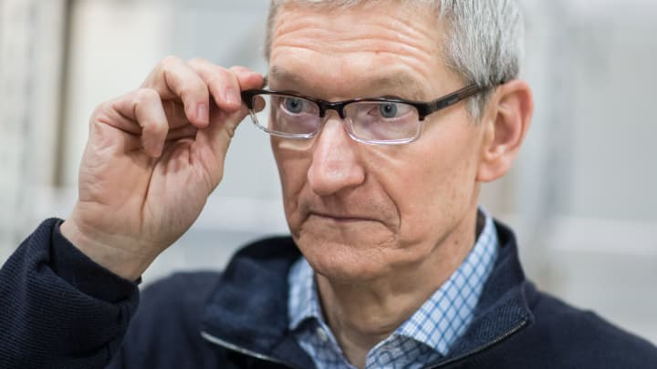 Apple CEO Tim Cook looks at a table during a visit of the shopfitting company Dula that delivers tables for Apple stores worldwide in Vreden, western Germany, on February 7, 2017.