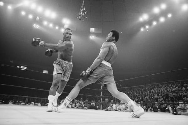 Boxer Muhammad Ali steps away from a punch thrown by boxer Joe Frazier during their heavyweight title fight at Madison Square Garden in 1971.