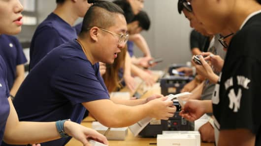 People purchase iPhones at an Apple store in Beijing, China.