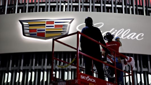 A worker wipes the logo of the General Motors Cadillac brand display ahead of the 2017 New York International Auto Show (NYIAS) in New York earlier this year.