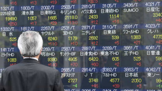A businessman looks at an electronic share indicator at the window of a securities company in Tokyo on April 24, 2017.