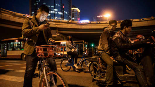 A commuter checks his mobile phone while using a bike share on March 27, 2017 in Beijing, China. Mobile payments platforms in China are used for everything from renting bicycles to paying for restaurant bills.