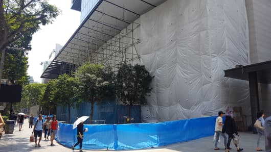 Pedestrians walk by an Apple store under construction in Singapore.