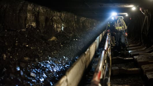 A coal miner shines his head lamp on coal transported on a conveyor belt after being sheared off the wall during longwall mining operations at the Consol Energy Bailey Mine in Wind Ridge, Pennsylvania.