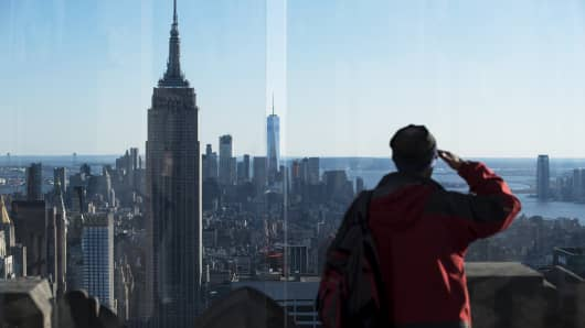 A visitor looks out at the city from the top of 30 Rockefeller Plaza, in New York, March 29, 2017. President Donald Trump and House Republicans are making the latest push to end the federal deduction for state and local taxes, which would challenge longstanding tradition and powerful opponents, in wealthy and populous states.