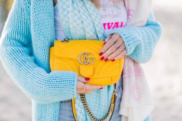 Model and fashion blogger Alexandra Lapp holds a a yellow Gucci GG Marmont bag.