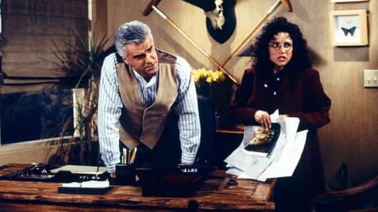 "John O'Hurley as J. Peterman, left, and Julia Louis-Dreyfus as Elaine in ""Seinfeld."""
