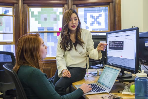 Diane Kim, an interaction designer at x.ai, talks with Raquel Ledezma-Haight, a customer experience associate, at the office in New York, March 21, 2017. Kim's job to craft responses for the company's assistants, who are named Andrew and Amy Ingram, or AI for short, that feel natural enough that swapping emails with these computer systems feels no different than emailing with a human assistant