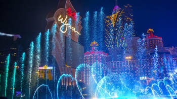 Water from a fountain sprays into the air in front of signage for the Wynn Macau casino resort.