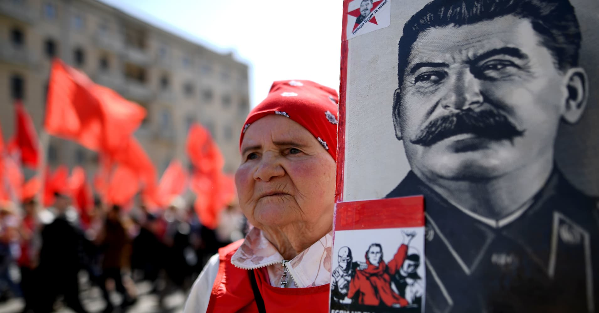 A Russian Communist party activist carries a banner with a portrait of late Soviet leader Joseph Stalin during a May Day rally in central Moscow on May 1, 2017.