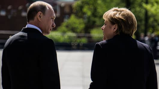Russian President Vladimir Putin and German Chancellor Angela Merkel attend a wreath laying ceremony at the Unknown Soldiers's Tomb on May 10, 2015 in Moscow, Russia.
