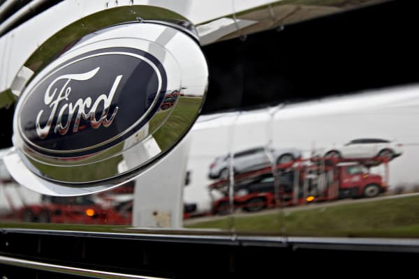 A passing car carrier is reflected in the grille of a 2017 Ford Motor Co. F-150 pickup truck on display at the Sutton Ford Lincoln car dealership in Matteson, Illinois.