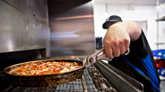 An employee removes a pizza from the oven at a Domino's Pizza restaurant in Rantoul, Illinois.