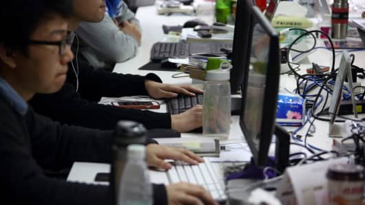 Workers use computers on their desks inside Tech Temple, a co-working space for start-up companies sponsored by Infinity Ventures Partners, in Beijing, China, on Thursday, March 12, 2015.
