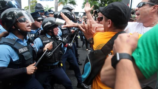 Demonstrators and police clash during a protest against the government's austerity measures as Puerto Rico faces a deadline on Monday to restructure its $70 billion debt load or open itself up to lawsuits from creditors, in San Juan, Puerto Rico May 1, 2017.