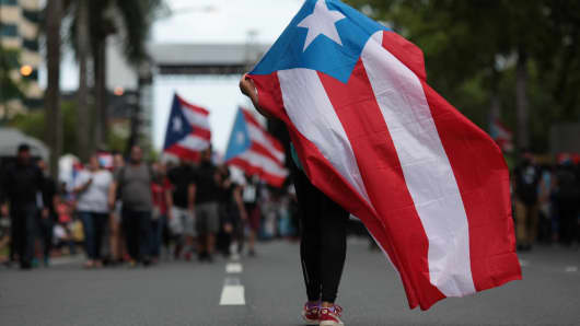 A person carries a Puerto Rican national flag during a protest against the government's austerity measures as Puerto Rico faces a deadline on Monday to restructure its $70 billion debt load or open itself up to lawsuits from creditors, in San Juan, Puerto Rico May 1, 2017.