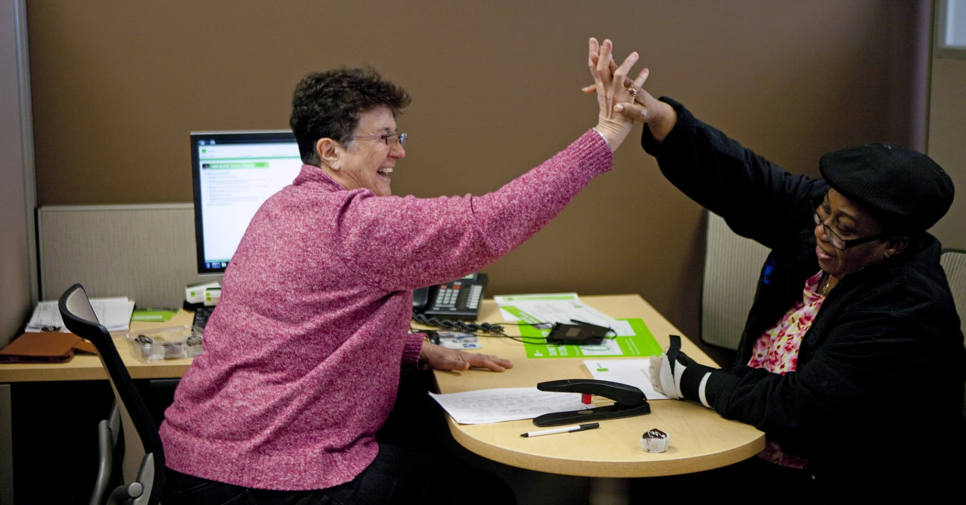 H&R Block employee high fives a customer.