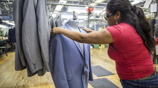 An employee inspects the quality of a finished suit jacket at the Joseph Abboud Manufacturing facility in New Bedford, Massachusetts.
