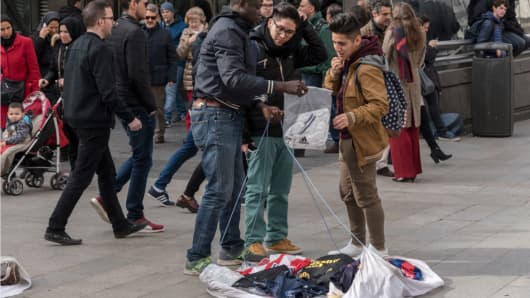 Street vendors, known as 'manteros' display their goods in Sol on February 16, 2017 in Madrid, Spain. The 'manteros', mostly African immigrants who offer counterfeit handbags, cheap t-shirts and shoes, engage in a continuous hide-and-seek game with the police trying to prevent their illegal activity.