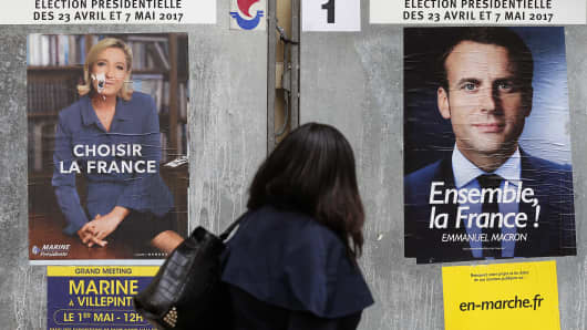 A woman looks at electoral posters of French presidential election for the En Marche ! (Onwards !) movement Emmanuel Macron and President of the National National Front (FN) Marine Le Pen, candidates for the French presidential election on May 04, 2017 in Paris, France.