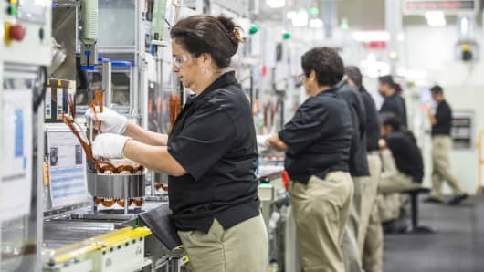 Employees build components for hybrid electric vehicle motors at the Toshiba International manufacturing facility in Houston, Texas.