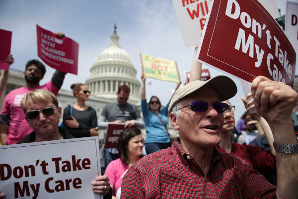 Activists hold signs during a Stop 'Trumpcare' rally in front of the Capitol in Washington, DC.