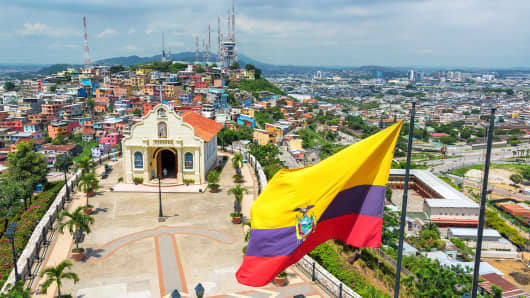 Ecuadorian flag on top of Santa Ana hill with a church and the city of Guayaquil visible in the background in Ecuador.