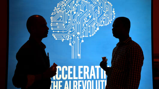 Participants at Intel's Artificial Intelligence (AI) Day stand in front of a poster during the event in the Indian city of Bangalore on April 4, 2017.