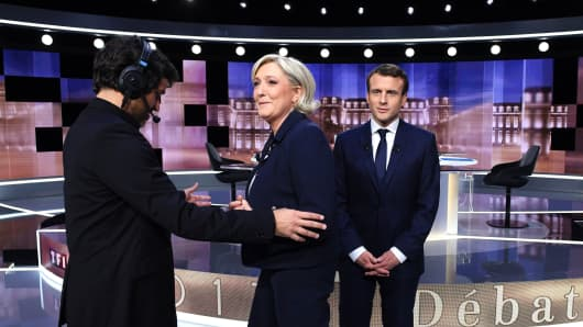Marine Le Pen and Emmanuel Macron arrive to pose prior to the start of a live brodcast face-to-face televised debate on May 3, 2017.