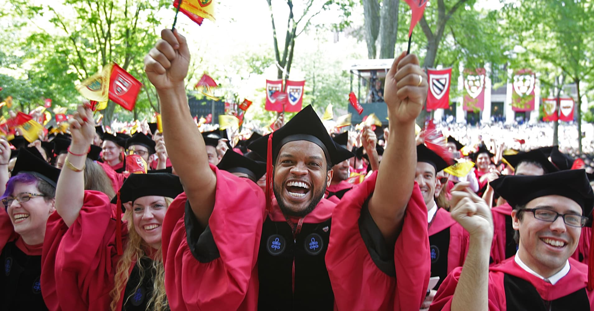 Students react as they prepare to receive their diplomas at commencement at Harvard University.